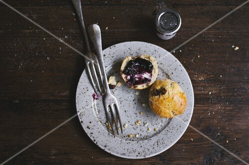 Breakfast bun with blueberry jam on a plate with a fork