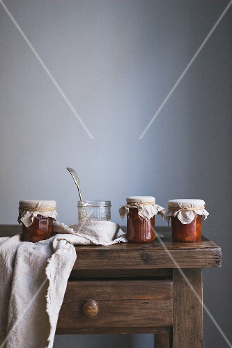 Jars of peach jam on a wooden table