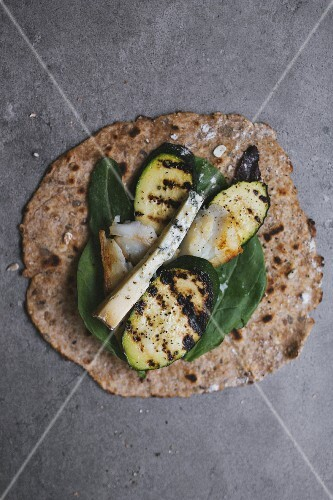 A wholemeal tortilla topped with grilled vegetables and cheese