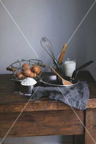 Ingredients and baking utensils for making crêpes on a wooden table