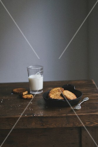 Freshly baked cookies and a glass of milk on a wooden table