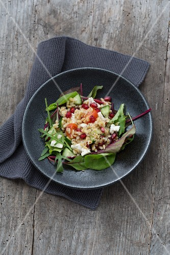 Barley salad with feta cheese and vegetables on a bed of lettuce