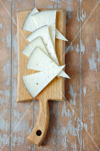 Triangles of Manchego cheese on a chopping board (seen from above)