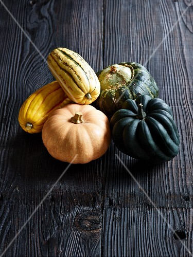 Various types of squash on a grey wooden surface