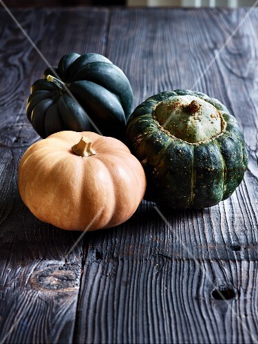 Three squash on a grey wooden table