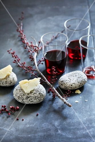 Red wine and pieces of cheddar cheese on stones