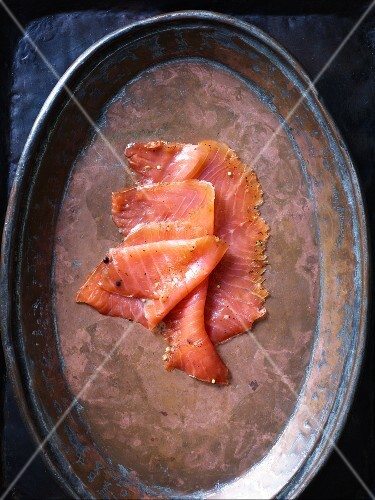 Thin slices of salmon on a copper plate
