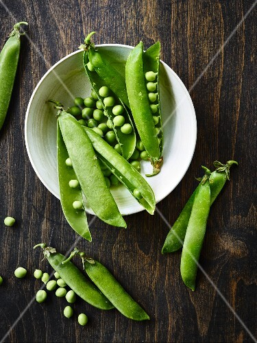 Fresh peas and pea pods on a wooden table