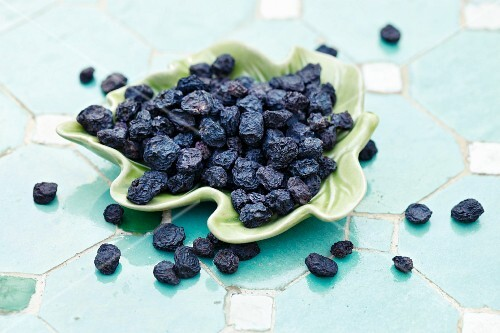 Dried aronia berries on a leaf-shaped dish