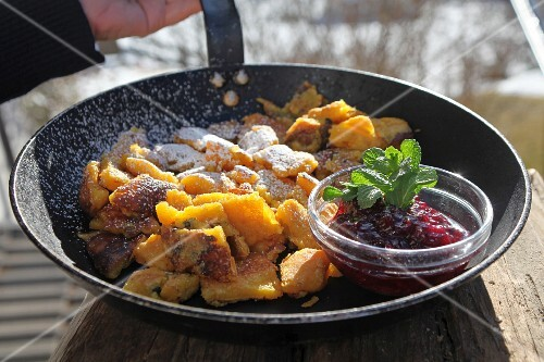 Kaiserschmarrn (shredded sugared pancake from Austria) with lingonberries, mint and icing sugar in a pan