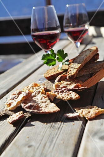 Schüttelbrot (crispy unleavened bread from South Tyrol) and Vinschgauer bread (rye-wheat sour dough) on a rustic wooden table with red wine
