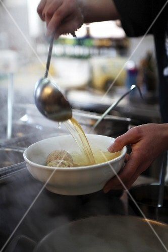 Dumpling soup being ladled into a bowl (South Tyrol)