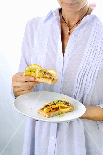 A woman holding a crostini with anchovies and oranges