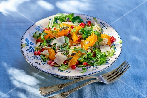 Rocket salad with oranges, pomegranate seeds, Parmesan cheese and pumpkin seeds