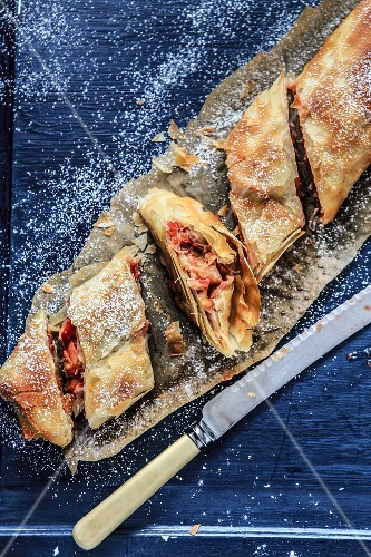 Rhubarb strudel dusted with icing sugar, sliced