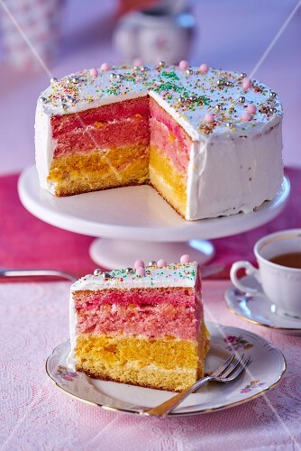 Rainbow cake decorated with sugar pearls, sliced