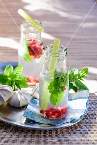 Lemon juice with pomegranate seeds and mint in bottles