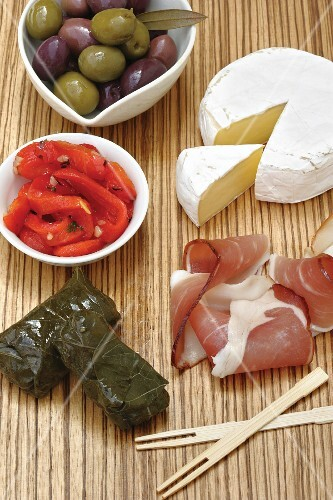 Various appetisers: olives, roasted peppers, cheese, ham and dolmades