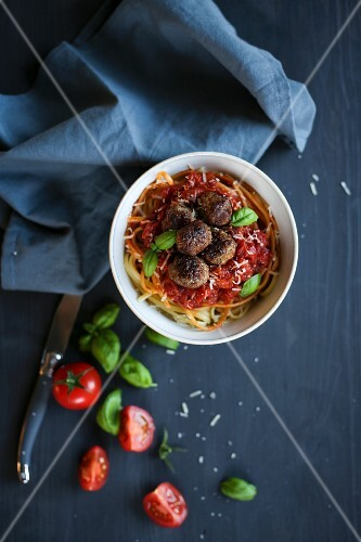 Spaghetti with meatballs, tomato sauce and basil (seen from above)