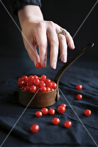 A hand taking mini redcurrant tomatoes from a copper pan