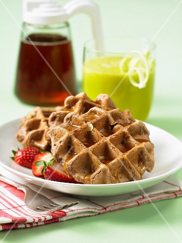 Vegan chocolate and hazelnut waffles with strawberries and maple syrup