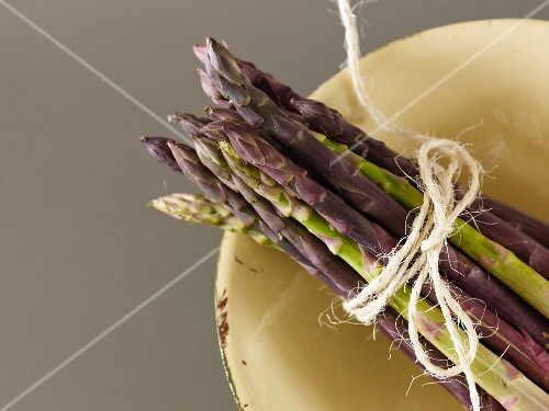 A bundle of green asparagus in a bowl