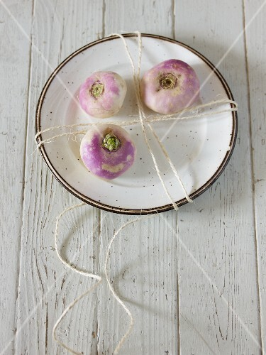 Three turnips on a plate with a piece of string
