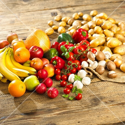 An arrangement of vegetables, mushrooms and fruit on a wooden table