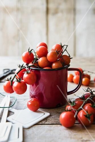 Vine tomatoes in a red enamel cup mug