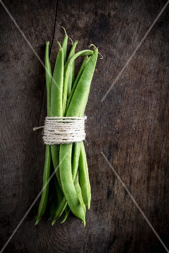 A bundle of green beans on a wooden board