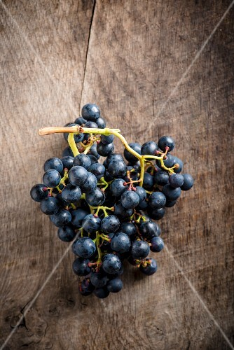 Red grapes on a wooden board (seen from above)