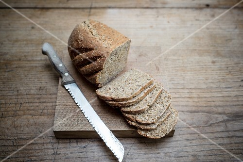 A loaf of sliced bread with a knife on a chopping board