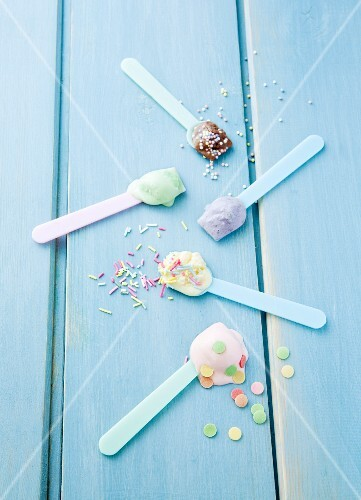 Various types of ice cream on ice cream spoons scattered with sugar sprinkles: vanilla, strawberry, chocolate, blueberry and mint