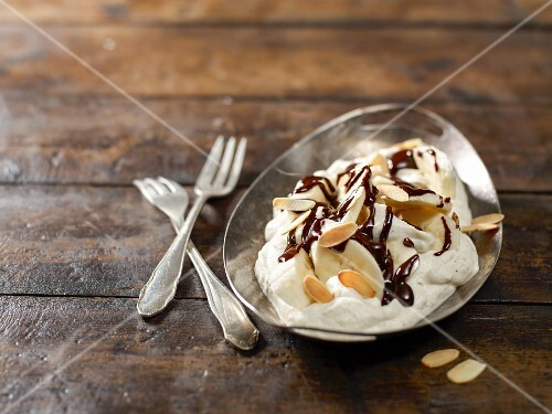 A banana split in a silver bowl on a wooden surface