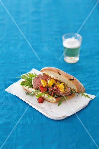A steak sandwich with braised tomatoes and rocket
