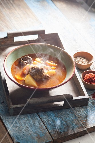 Steaming goulash soup in a bowl on a wooden tray