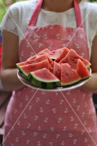 A woman wearing an apron holding a plate of melon slices