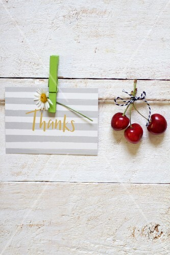 A thank you card and three red cherries hanging on a line