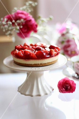 A mini strawberry tart on a cake stand