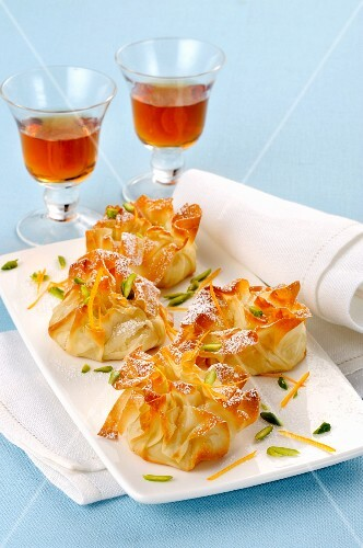 Sweet filo pastry sacks with pistachios and icing sugar served with dessert wine