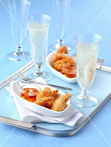 Fried sesame seed prawns with a chilli dip and glasses of champagne