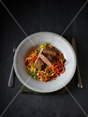 Lamb fillet on a bed of Brussels sprouts and carrot pasta