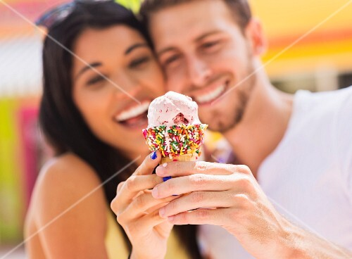 A couple sharing an ice cream cone
