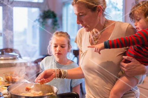 A woman cooking with children