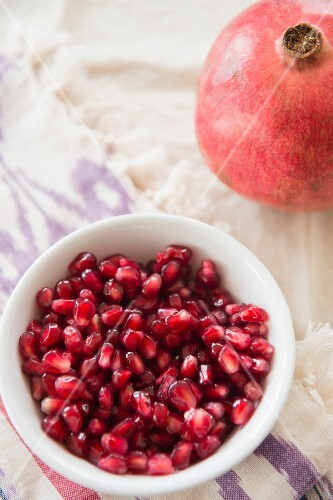 A whole pomegranate and a bowl of pomegranate seeds