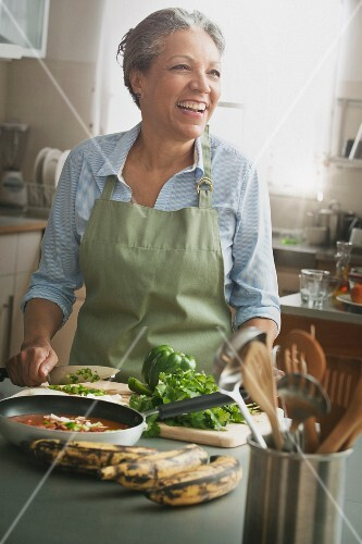 An older woman in a kitchen slicing vegetables