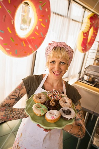 A blonde woman holding a selection of doughnuts on a plate