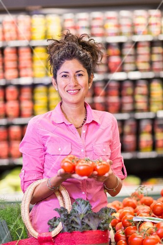 A woman in a supermarket holding tomatoes