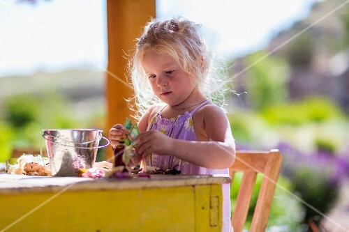 A little girl playing with dolls at a table on the terrace