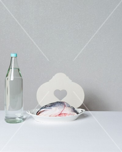 A salmon head on a porcelain plate next to a bottle of water